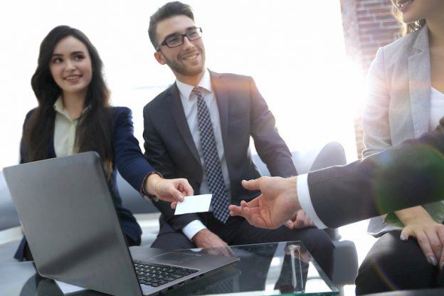 Eine Frau überreicht bei einem Bewerbungsgespräch eine Visitenkarte