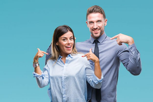 Mann und Frau in Geschäftskleidung zeigen für ihre Bewerbungshomepage auf sich selbst