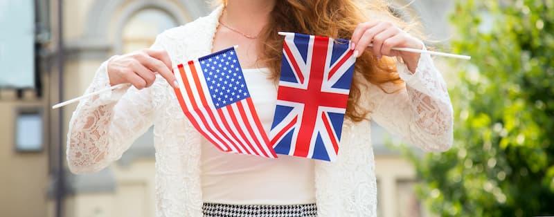 Frau hält Flaggen der USA und GB in der Hand