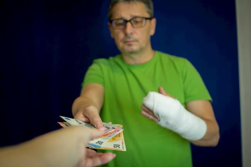 Ein Mann bekommt Geld und hat eine gebrochene Hand