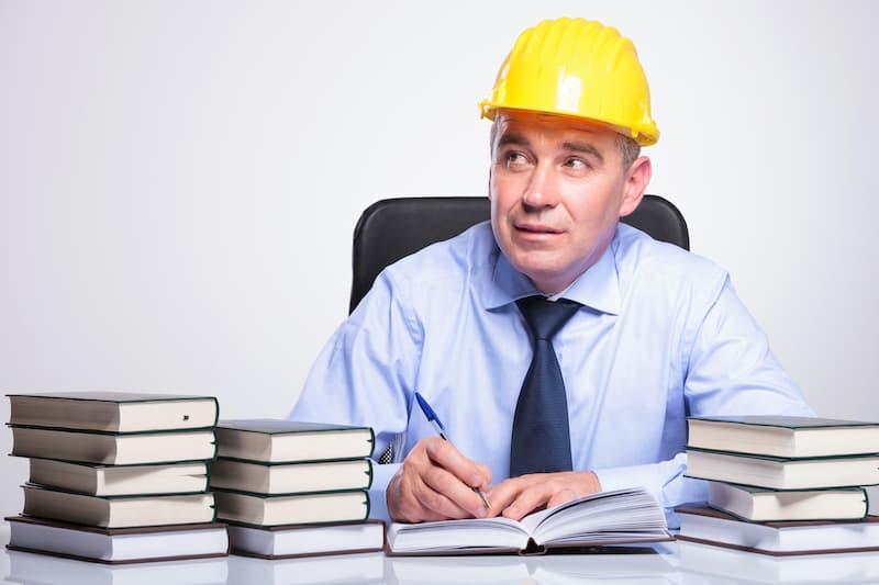 Ein Betriebsratsmitglied sitzt zwischen Büchern und liest etwas nach