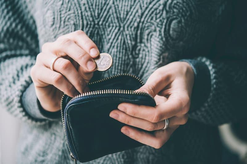Ein Mensch hält eine Euromünze und eine Geldbörse