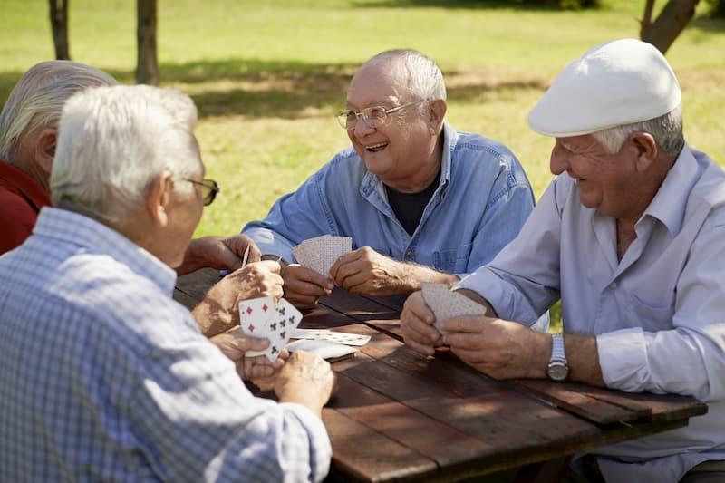 Ein paar alte Männer spielen am Vormittag Karten im Park, da sie bereits den Renteneintritt absolviert haben