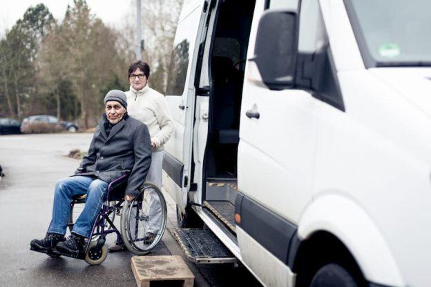 Eine Frau bei einer Taxifahrt mit einem Menschen im Rollstuhl, ein potenzieller Job für Rentner