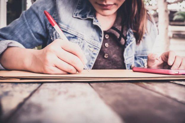 Eine junge Frau schreibt ihr Berichtsheft