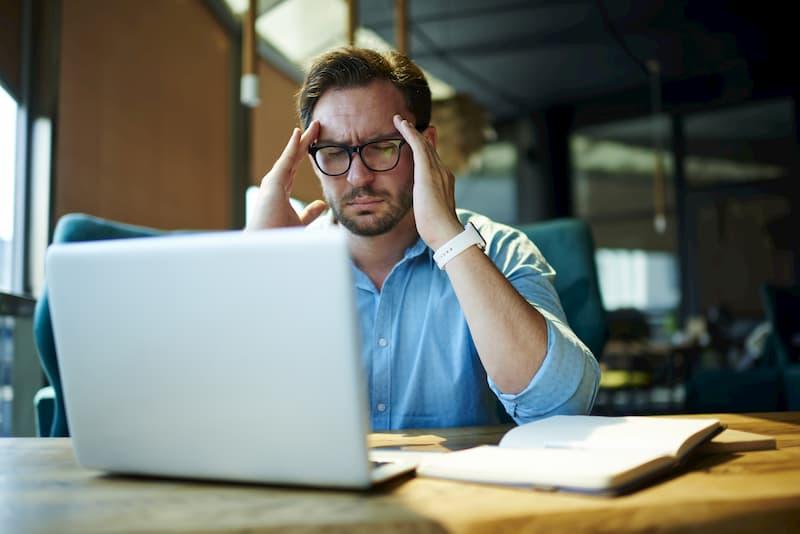 Ein junger Mann sitzt nachdenklich vor dem Laptop und möchte den Ausbildungsvertrag kündigen