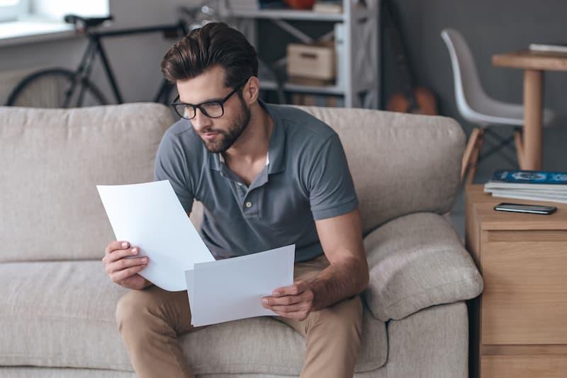 Ein junger Mann sitzt auf dem Sofa und liest seinen Ausbildungsvertrag durch