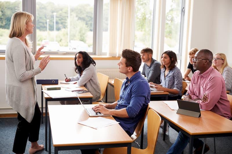 Menschen machen Bildungsurlaub und sitzen in einem Kurs an Tischen