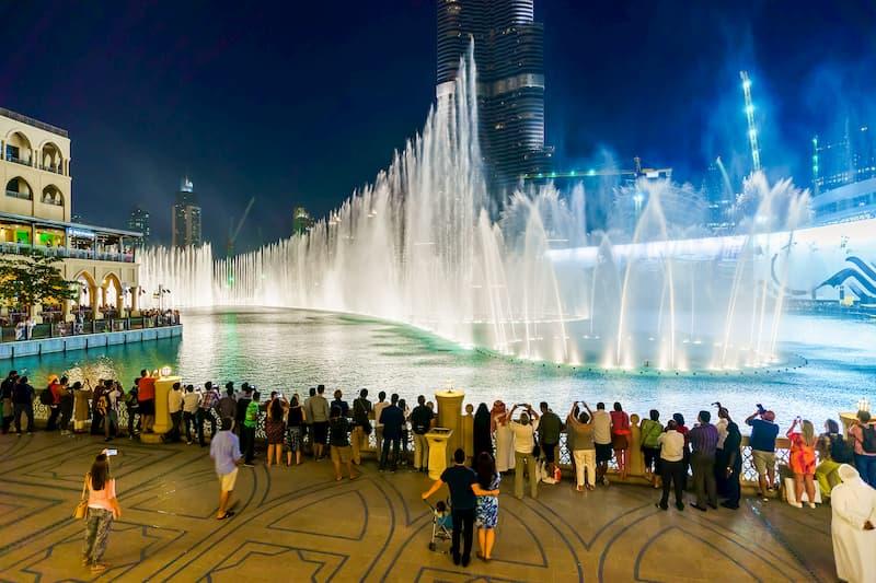 Eine Menschengruppe vor den Wasserspielen in Dubai, bei kostspieligen Reisen hilft Urlaubsgeld