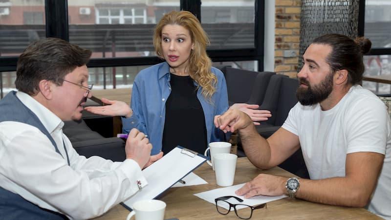 Eine Frau hilft bei einem Konflikt am Arbeitsplatz, der zwischen zwei Männern stattfindet