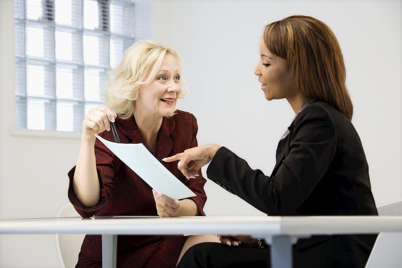 Eine Frau hilft einer anderen Frau bei der Optimierung der Unterlagen beim Bewerbungscoaching