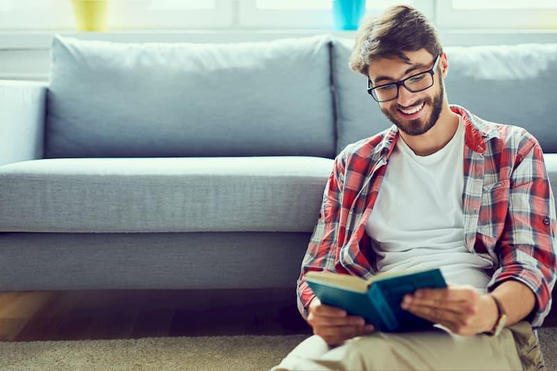 Ein junger Mann sitzt vor dem Sofa und liest ein Bewerbungsbuch