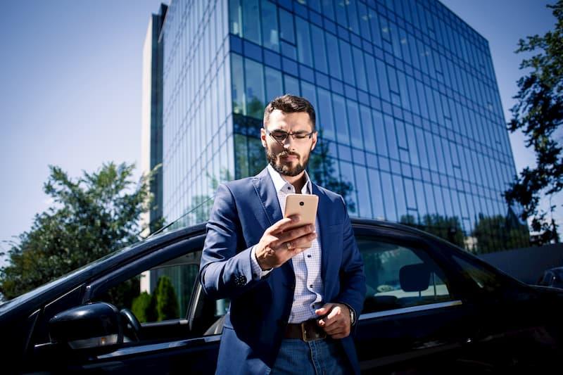 Ein Mitarbeiter steht mit dem Auto vor dem Büro und schaut nach ob er Tankgutscheine hat, diese können Teil einer betrieblichen Übung sein