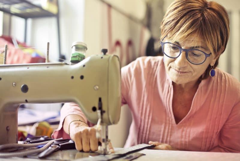 Eine ältere Frau ist in Altersteilzeit als Näherin angestellt