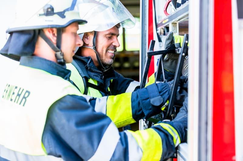 Feuerwehrmänner durchleuchten die Systeme des Feuerwehrautos, hier ist Bereitschaftsdienst üblich