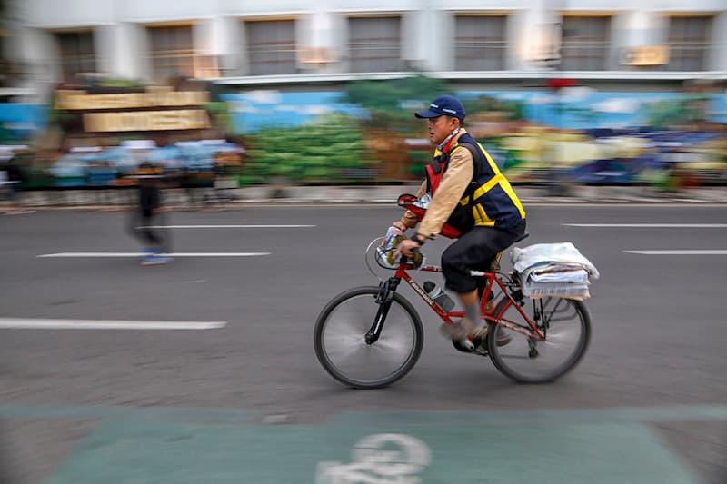 Ein Mann auf einem Fahrrad hat einen Nebenjob und trägt Zeitungen aus