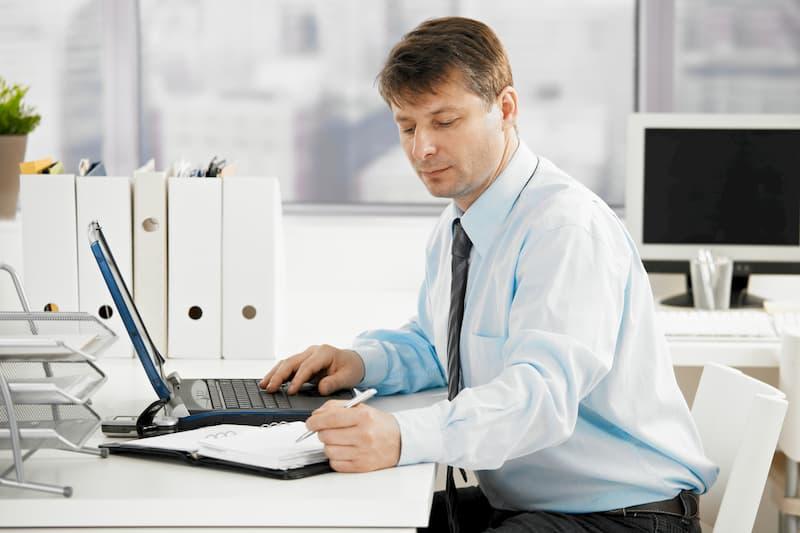 Ein Mann notiert per Hand seine Überstunden