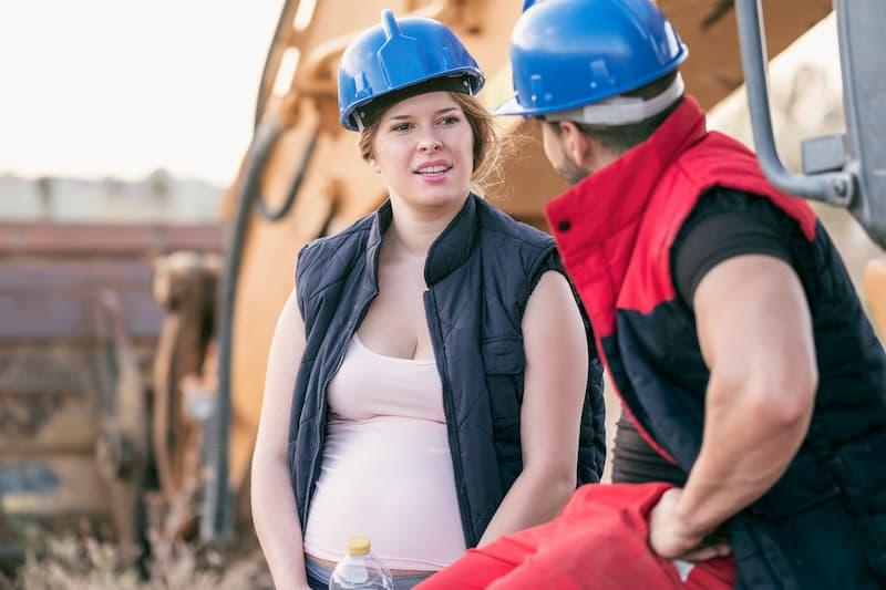 Eine schwangere Frau mit einem Arbeiter auf der Baustelle - sie könnte von einem Beschäftigungsverbot profitieren