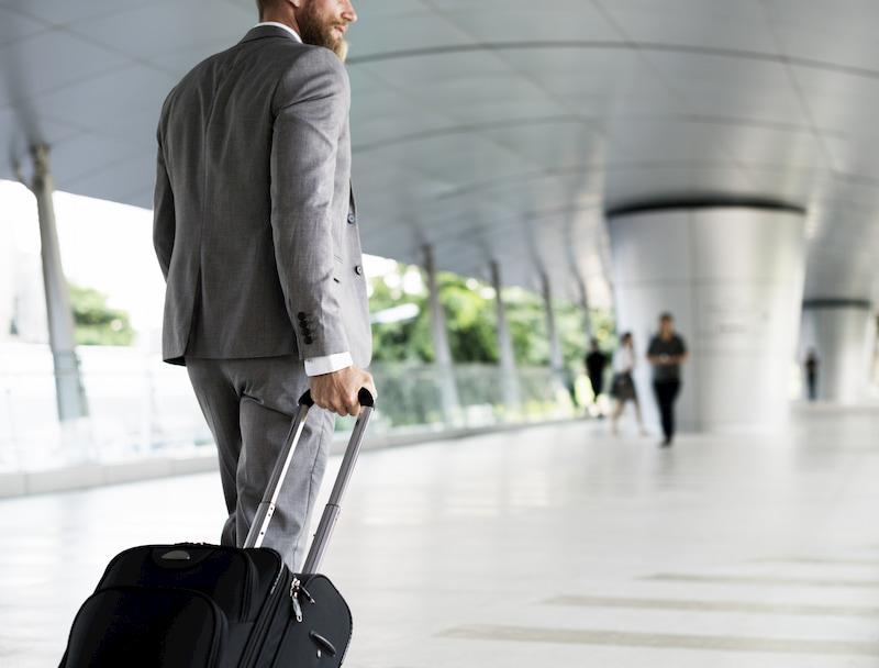 Ein Mann im Anzug ist mit einem Koffer auf Dienstreise