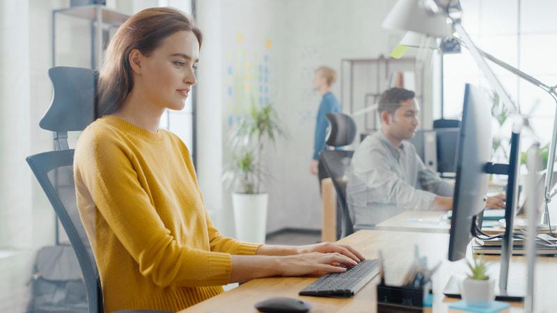 Im Rahmen des betrieblichen Eingliederungsmanagements sitzt eine Mitarbeiterin am Arbeitsplatz auf einem ergonomischen Stuhl