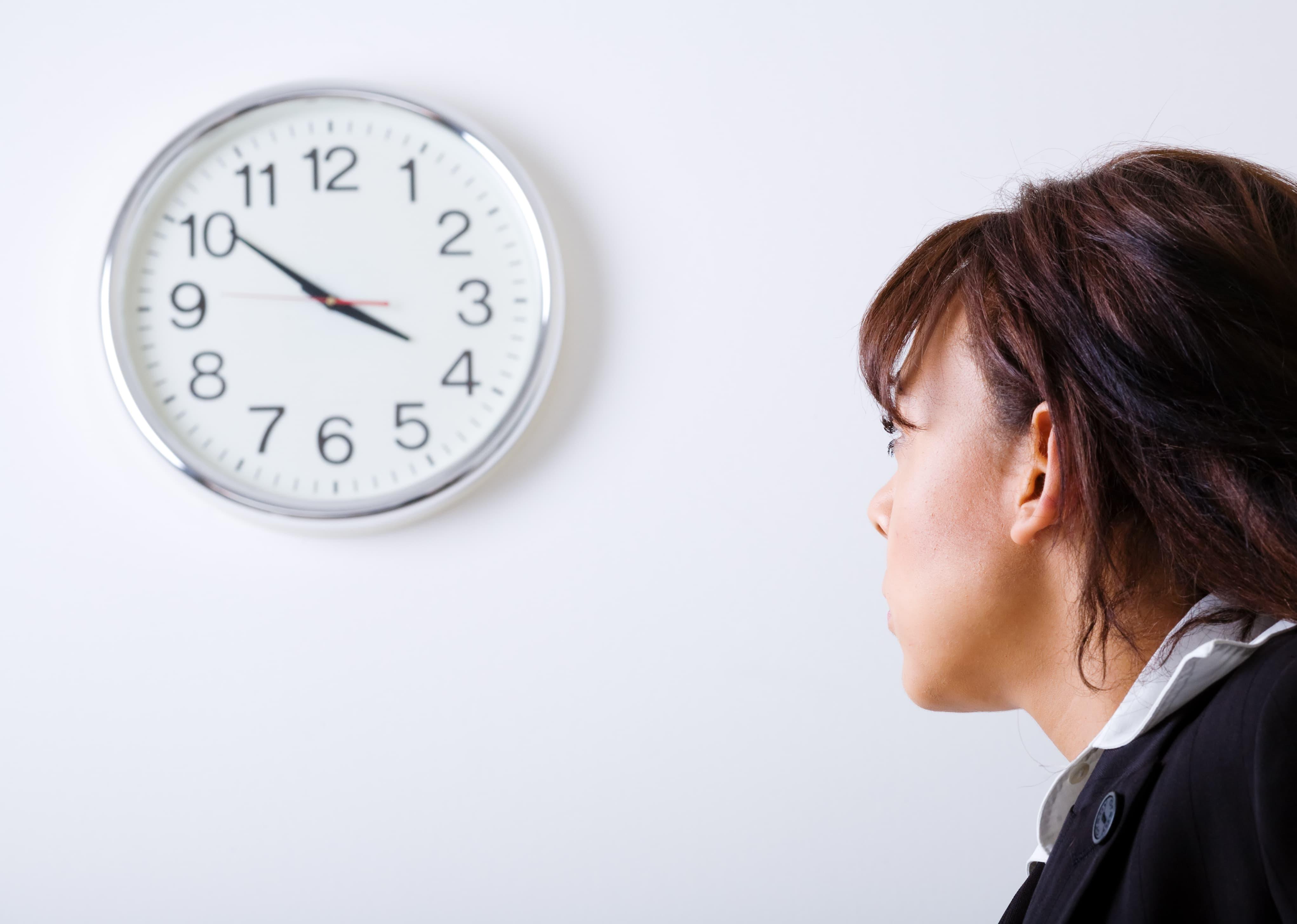 Eine Frau arbeitet nach Vertrauensarbeitszeit und schaut auf die Uhr