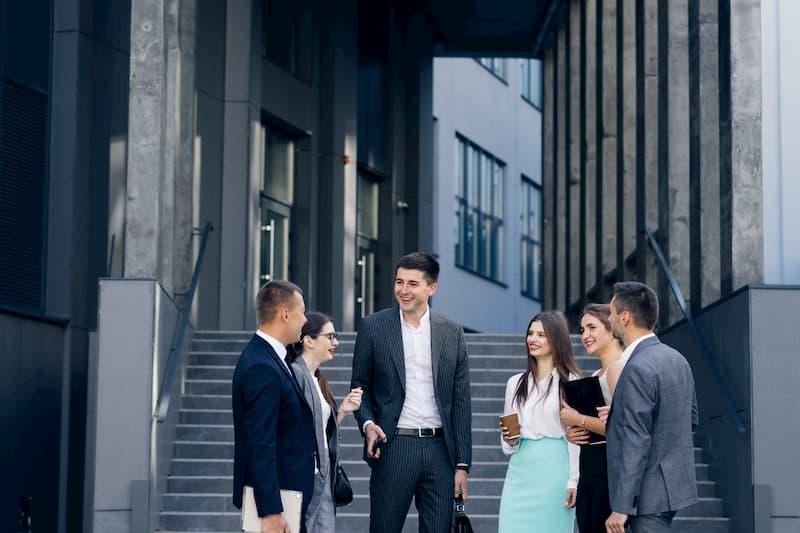 Ein Chef steht mit Mitarbeitern vor der Firma und pflegt einen bestimmten Führungsstil