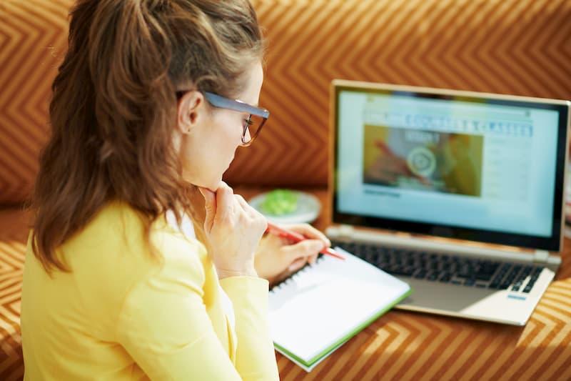 Eine junge Frau macht ein Fernstudium und lernt auf dem Laptop