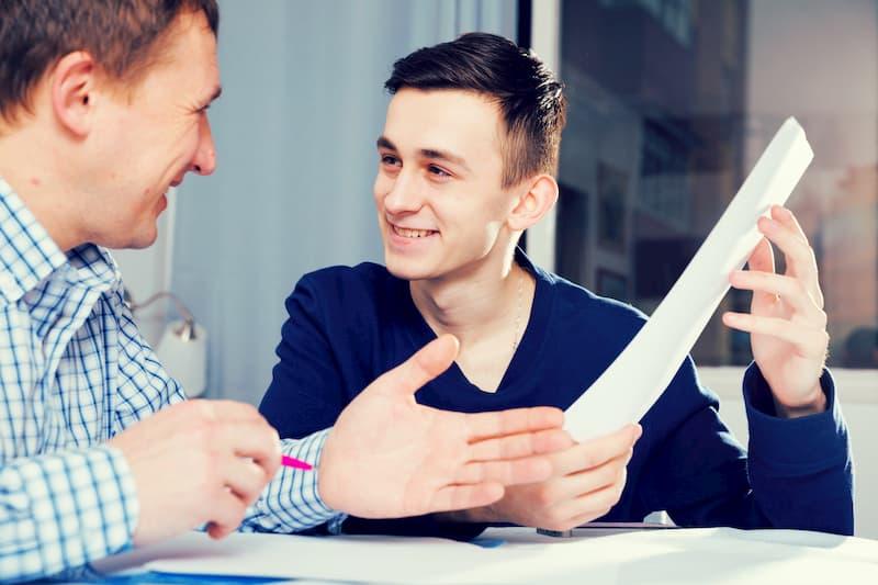Ein junger Mann erhält von seinem Chef ein einfaches Arbeitszeugnis