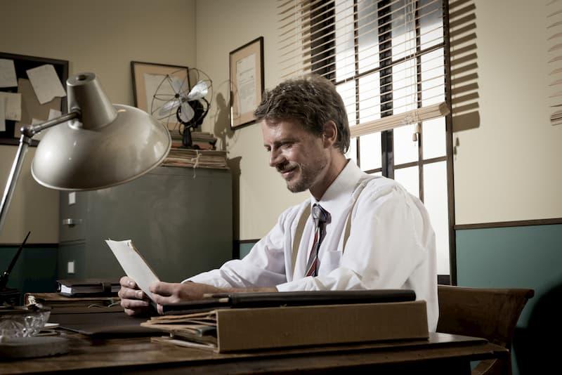 Ein Mann sitzt am Schreibtisch und hält ein Arbeitszeugnis in der Hand, welche nach einem Muster entstand