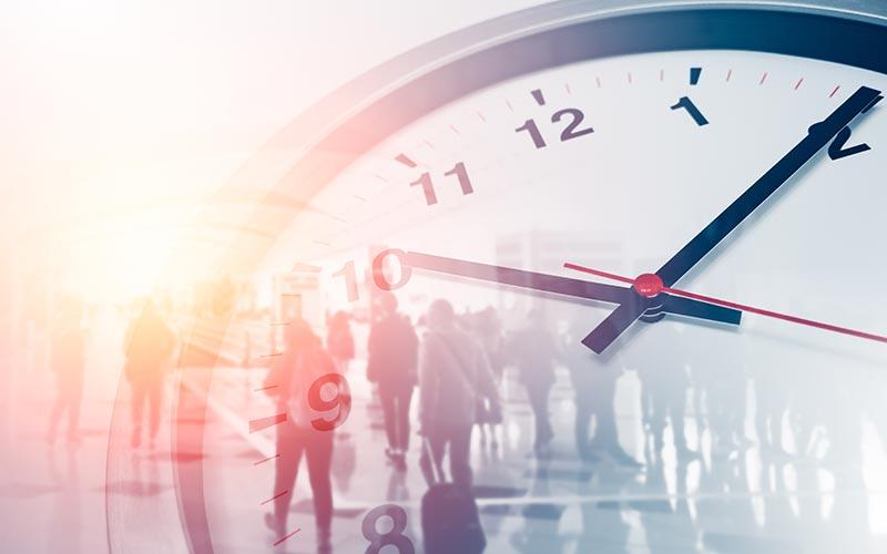 Symbolbild, Menschen im Büro und eine übergroße Uhr