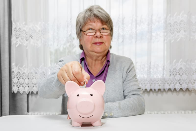 Ein Frau wirft Geld in ein Sparschwein, da sie keine betriebliche Altersvorsorge hat