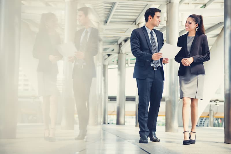 Eine Geschäftsfrau im Gespräch mit einem Geschäftsmann, es herrscht ein Dresscode