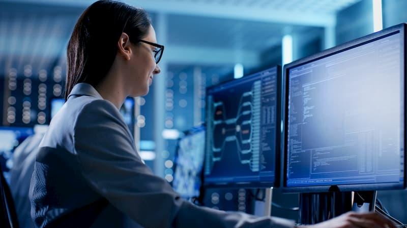 Eine Frau sitzt am Computer und bearbeitet Daten, diese sind Teil des Betriebsgeheimnisses