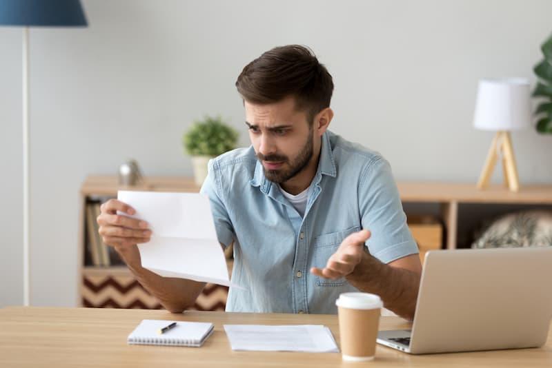 Ein Mann sitzt am Tisch, liest einen Brief und ärgert sich über die Vertragsstrafe