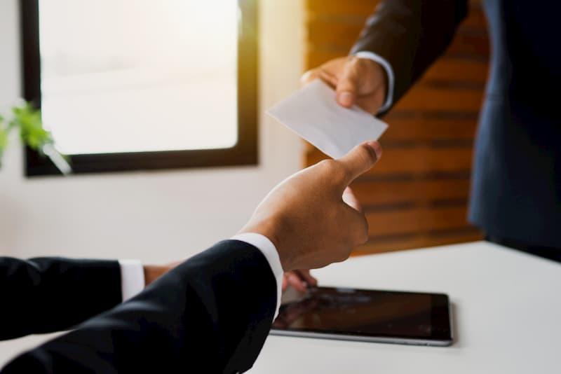 Ein Mann erhält eine Karenzentschädigung in einem Briefumschlag