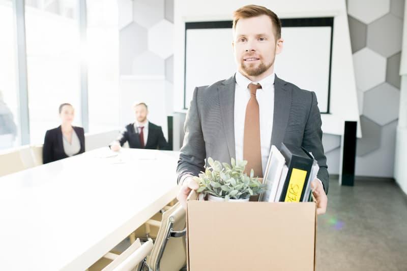 Ein Mann hat einen Karton in der Hand und verlässt nach ordentlicher Kündigung das Büro