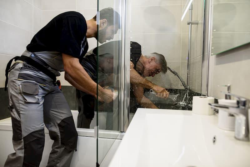 Zwei Klempner im Bad bei der Arbeit, sie tragen Arbeitskleidung