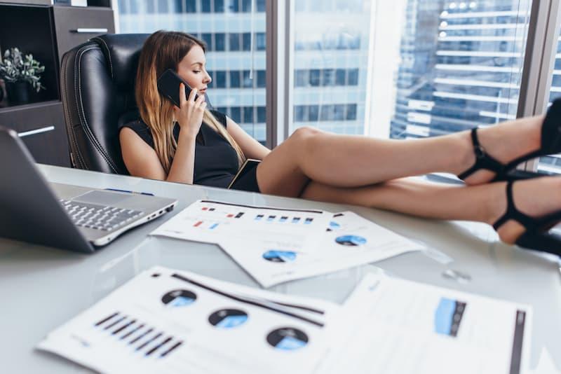 Eine Frau legt die Füße auf den Tisch und telefoniert am Arbeitsplatz, dies ist manchmal Arbeitsverweigerung