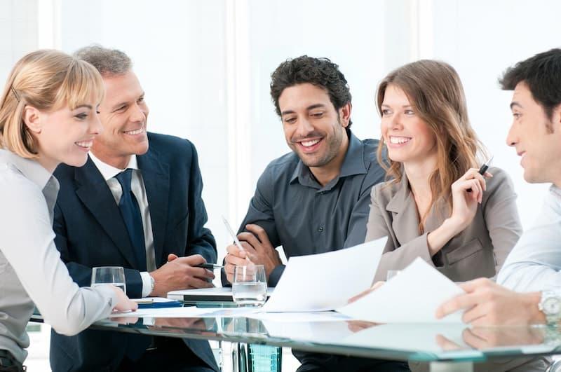Eine Gruppe von Mitarbeitern mit ihrem Geschäftsführer, sie freuen sich über eine Vereinbarung mit neuen Mitarbeiter-Benefits
