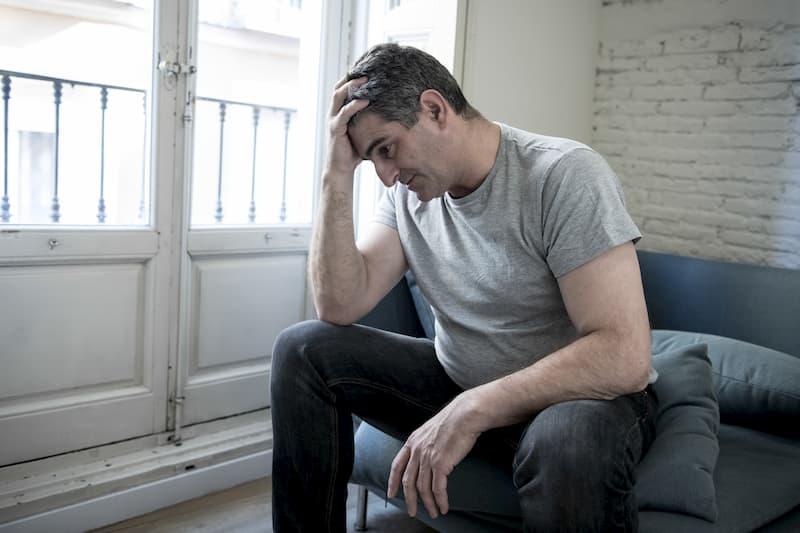 Ein Mann hält sich den Kopf und fühlt sich schlecht aufgrund von Stress