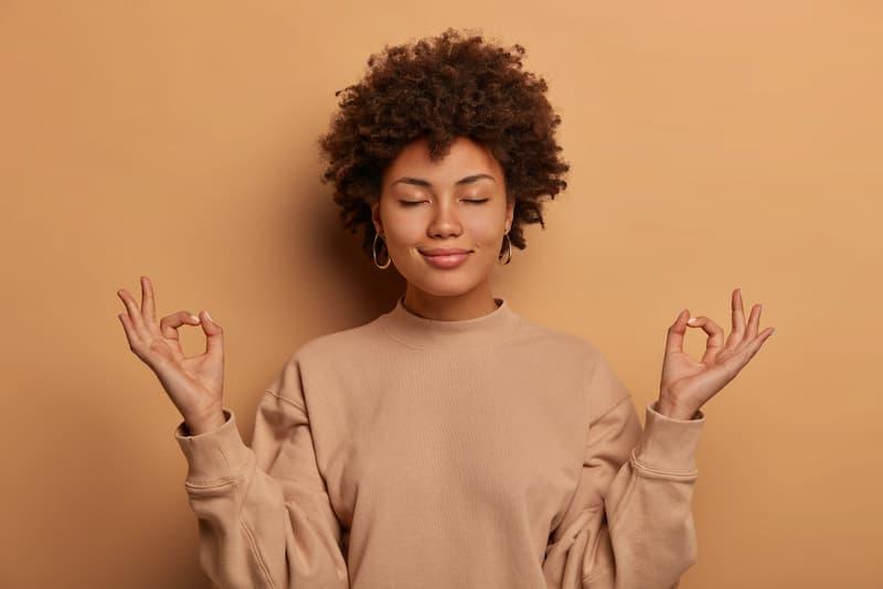 Eine Frau übt Geduld und macht eine Meditationsgeste