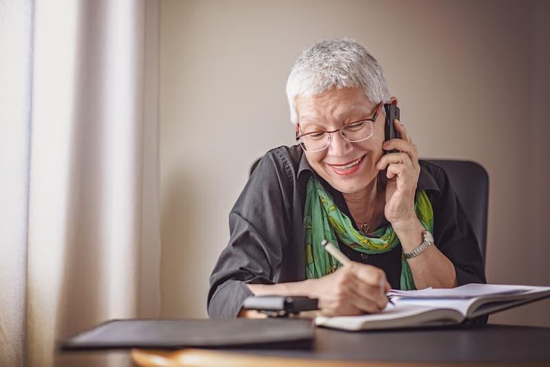 Eine alte Frau schreibt etwas in ein Buch, sie bereitet sich auf den Ruhestand vor