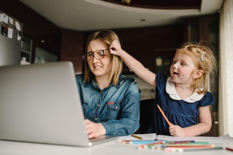 Eine Frau mit ihrem Kind, während sie arbeitet. Beides zusammen ist eine Doppelbelastung