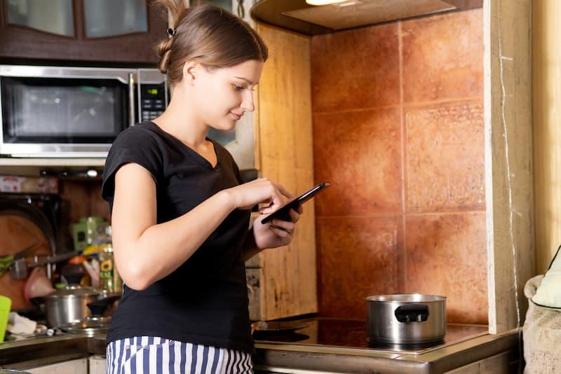 Eine Frau kocht sich in der eigenen Küche essen, muss aber aufgrund Rufbereitschaft per Smartphone erreichbar sein