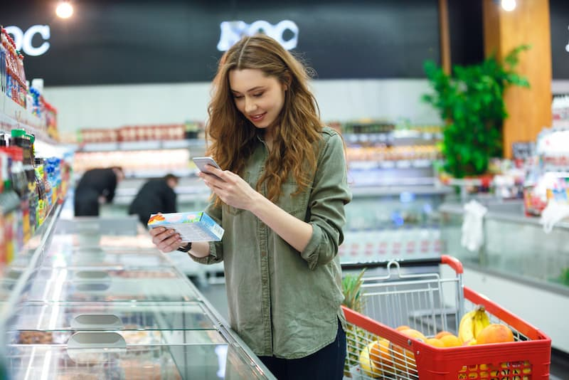 Frau beim Crowdworking mit dem Smartphone im Supermarkt