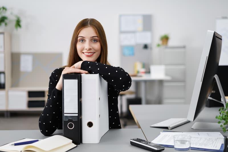Eine junge Frau sitzt glücklich am Schreibtisch, sie macht eine Umschulung zur Bürokauffrau