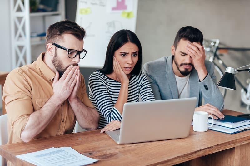 Mehrere Mitarbeiter sitzen frustriert vor dem Laptop, da eine Urlaubssperre verkündet wurde