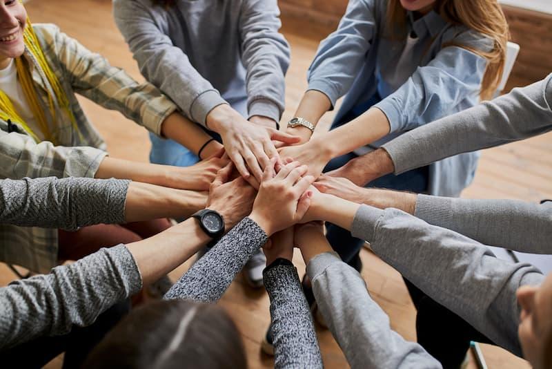 Menschen legen ihre Hände aufeinander um ein Zeichen für Teamwork zu zeigen