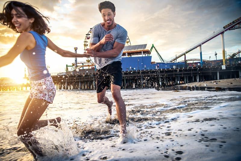 Ein Paar läuft durch das Wasser am Strand von Los Angeles, sie verbringen dort ihren Erholungsurlaub