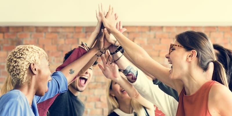 Ein Team schlägt die Hände ein, sie haben eine hohe soziale Kompetenz